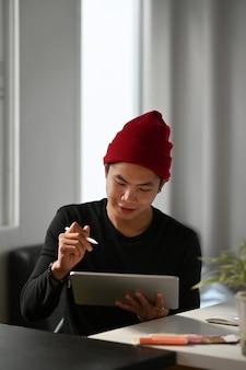 Retrato do designer gráfico ou fotógrafo está usando a caneta de desenho em um computador tablet portátil.