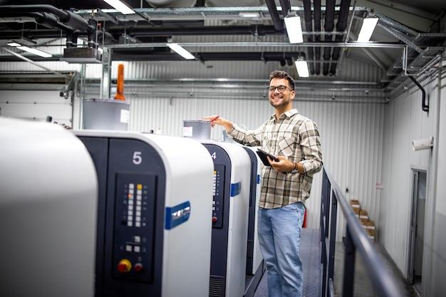 Retrato do designer gráfico verificando a produção na máquina de impressão offset na fábrica de impressão