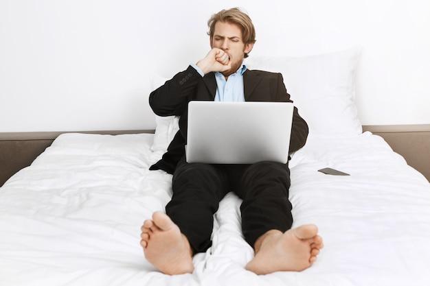 Retrato do diretor de empresa madura com sono deitado na cama, fechando a boca com a mão com a mão enquanto bocejando, trabalhando preguiçoso no laptop.
