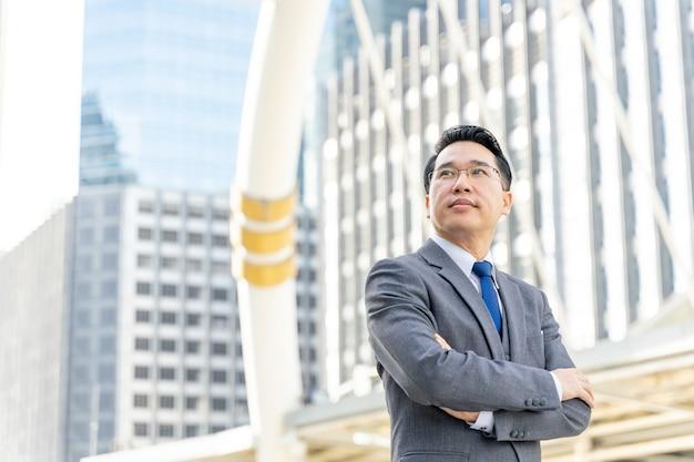 Retrato do distrito comercial de homem de negócios asiático, líder de executivos visionários sênior com visão de negócios - conceito de estilo de vida de pessoas