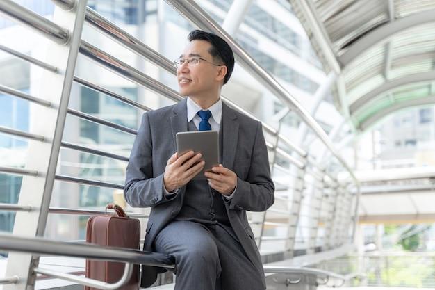 Retrato do distrito financeiro de homem de negócios asiático, líder de executivos visionários sênior com computador de telefone visionado de negócios na mão - conceito de pessoas de negócios de estilo de vida