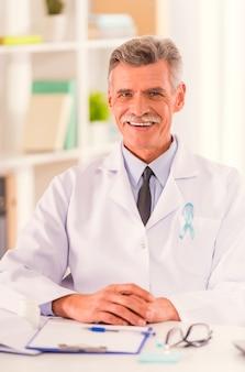 Retrato do doutor com a fita azul que senta-se em seu escritório.