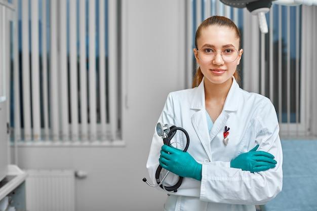 Retrato do doutor fêmea novo bem sucedido feliz que guarda um estetoscópio. conceito médico