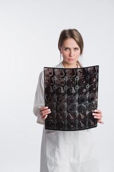 Retrato do doutor fêmea pensativo no uniforme branco que olha a imagem do raio x.