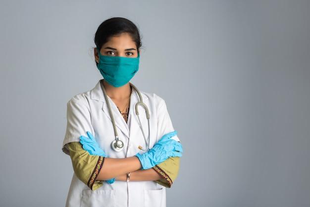 Retrato do doutor mulher vestindo uma máscara protetora e luvas com um estetoscópio. epidemia mundial do conceito de coronavírus.