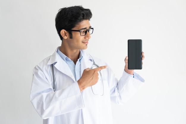 Retrato do doutor novo de sorriso nos vidros que mostram o telefone móvel.