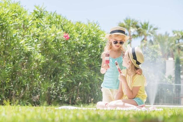 Retrato do duas meninas bonitos com sorvete. diversão no verão.