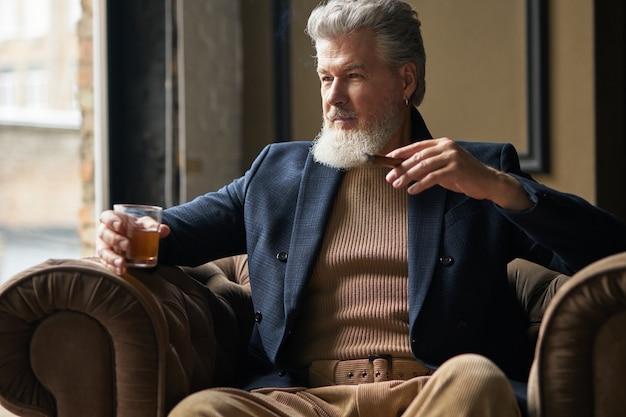 Retrato do elegante empresário maduro com barba, olhando para o lado, segurando um copo de uísque e