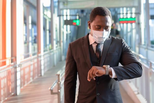 Retrato do empresário africano com máscara, verificando o tempo na estação de trem ao ar livre