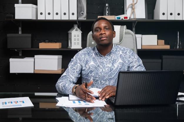 Retrato do empresário americano africano jovem bonito trabalhando com documentos e laptop no escritório