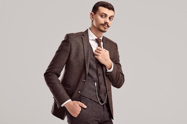 Retrato do empresário árabe confiante jovem bonito com bigode chique em terno completo marrom de lã no fundo do estúdio