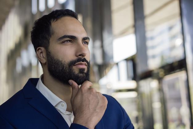 Retrato do empresário árabe pensativo, em pé no escritório, planejando o arranque. negócio de sucesso