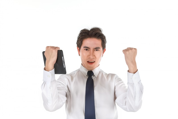 Retrato do empresário asiático jovem inteligente, vestindo camisa branca, segurando os sentimentos de tablet computador contente e levantou o punho dois