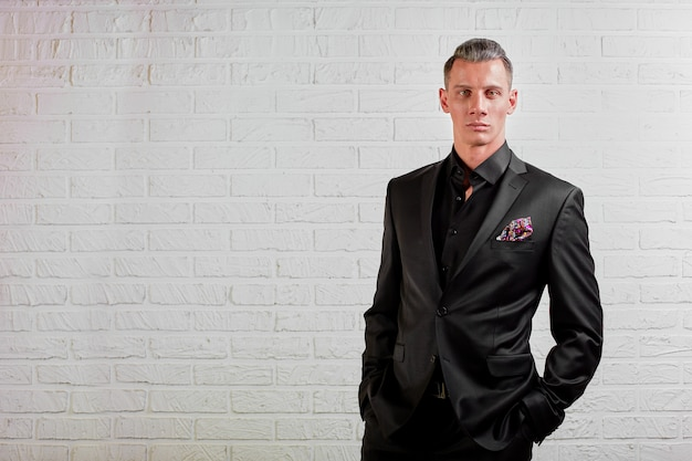 Retrato do empresário bonito terno preto em pé no espaço da cópia de fundo de parede
