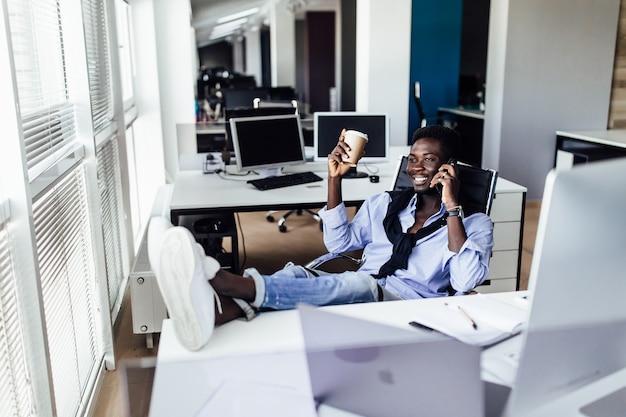 Retrato do empresário branco trabalhando no projeto em um escritório moderno, segurando o café e relaxante.