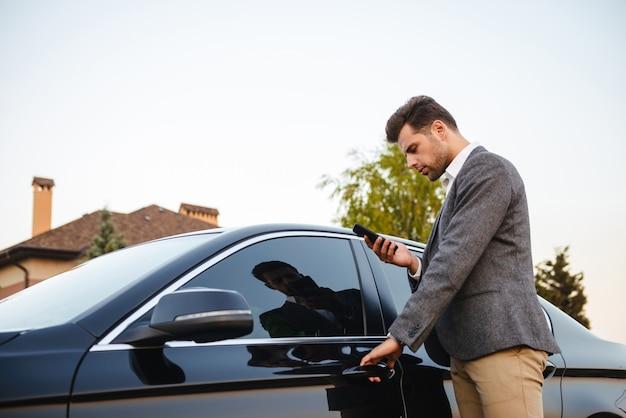 Retrato do empresário caucasiano vestindo terno, abrindo a porta do motorista do seu carro de luxo preto e usando o smartphone