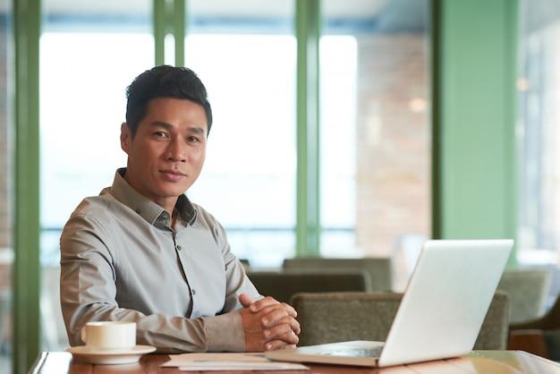 Retrato do empresário de meia-idade asiático, sentado na mesa do escritório no laptop