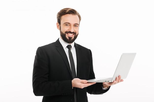 Retrato do empresário de sucesso sorrindo enquanto segura o laptop, isolado sobre a parede branca
