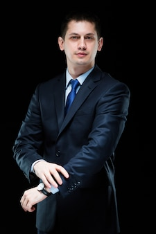 Retrato do empresário elegante bonito confiante com a mão em seu terno