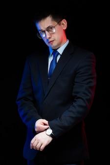 Retrato do empresário elegante bonito confiante em copos com a mão em seu terno em fundo preto