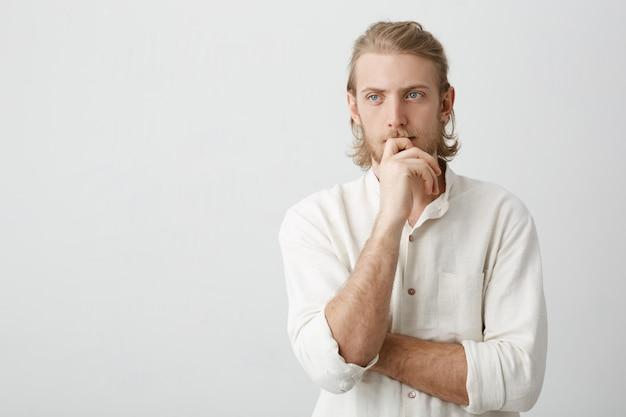 Retrato do empresário europeu atraente com penteado de rabo de cavalo e barba, segurando a mão no queixo enquanto olha de lado