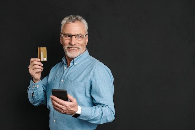 Retrato do empresário idoso dos anos 70 com cabelos grisalhos e barba segurando o cartão de crédito e smartphone para pagar on-line, isolado sobre parede preta