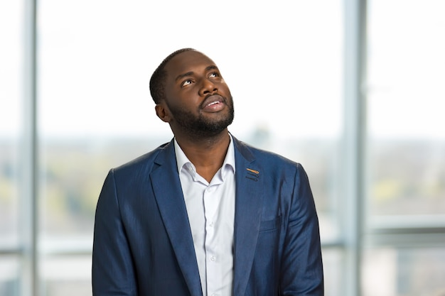 Retrato do empresário olhando para cima. homem bonito com roupa formal em pé e olhando para cima.