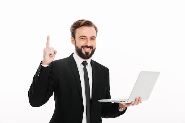 Retrato do empresário satisfeito, sorrindo e apontando o dedo na copyspace, mantendo o laptop, isolado sobre a parede branca