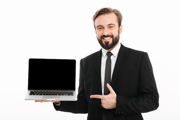 Retrato do empresário satisfeito, sorrindo e apontando o dedo na tela copyspace preto do laptop moderno na mão isolado sobre a parede branca