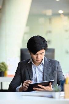 Retrato do empresário sentado na sala de conferências e trabalhando em tablet digital.