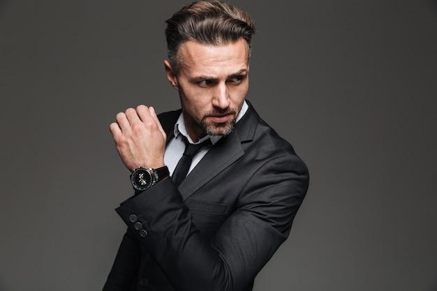 Retrato do empresário sério bonito terno preto, olhando de lado com relógio de pulso chique, isolado sobre o branco