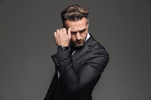 Retrato do empresário sério bonito terno preto, posando com relógio de pulso chique, isolado sobre grafite