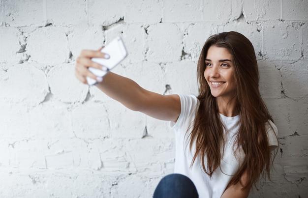 Retrato do encantador modelo feminino europeu, fazendo selfie em smartphone perto da parede de tijolo branco, sorrindo alegremente. blogueira da moda tira foto para postar em seu blog. ela tem muitos fãs.
