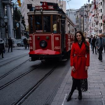 Retrato do estilo de moda de uma jovem mulher bonita posando na rua da cidade em taksim com o trem vermelho