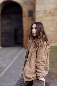 Retrato do estilo de moda. linda garota elegante com cabelo comprido caminha na cidade. retrato de uma garota atraente na rua. dia de primavera ou outono. foco seletivo.