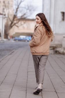 Retrato do estilo de moda. linda garota elegante com cabelo comprido caminha na cidade.