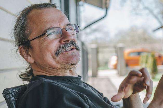 Retrato do estilo de vida casual de um homem maduro de cabelos grisalhos, óculos e bigode, falando com alguém e sorrindo