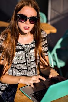 Retrato do estilo de vida da bela estudante ruiva, sentada no terraço do café, usando seu laptop