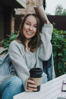 Retrato do estilo de vida da fêmea adulta jovem de suéter cinza, sentado ao ar livre com um copo para viagem cobrindo a cabeça com a bolsa da chuva e sorrindo para a câmera, foco seletivo