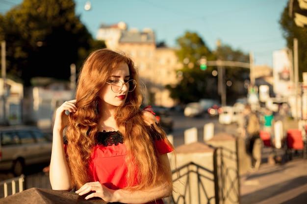 Retrato do estilo de vida da garota ruiva legal com sardas. modelo com cabelo longo cacheado de óculos. . espaço para texto