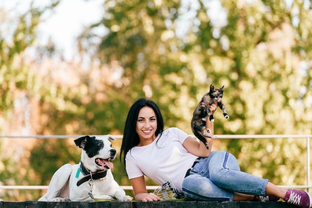 Retrato do estilo de vida da menina morena jovem bonita com pequeno gato e cachorro grande cão sentado ao ar livre no parque. feliz alegre sorridente adolescente abraçando animais de estimação adoráveis.