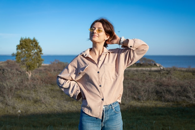 Retrato do estilo de vida da moda na moda jovem vestida de camiseta e calça jeans rindo, sorrindo, posando na praia