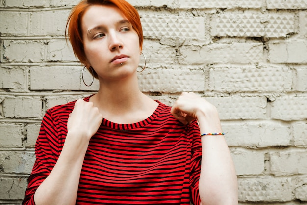 Retrato do estilo de vida da mulher branca adulta jovem na camisa despojada em frente à parede de tijolo, foco seletivo