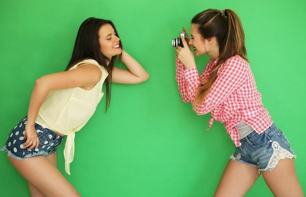 Retrato do estilo de vida de belas garotas de hipster de melhores amigos juntos com uma câmera fotográfica e se divertir enquanto uma foto tirada. sobre fundo verde. Foto Premium