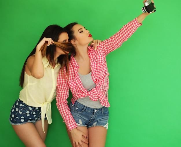 Retrato do estilo de vida de belas garotas de hipster de melhores amigos juntos com uma câmera fotográfica e se divertir enquanto uma foto tirada. sobre fundo verde.