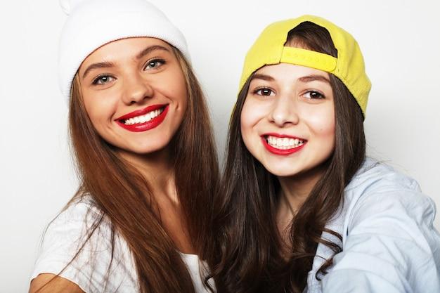 Retrato do estilo de vida de duas amigas muito adolescentes sorrindo e ha