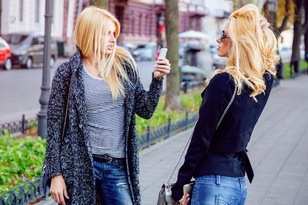 Retrato do estilo de vida de duas garotas loiras de duas melhores amigas, passando um tempo no centro da cidade em um belo dia de outono de outono, usando o smartphone, usando óculos escuros e aparência da moda da formiga.