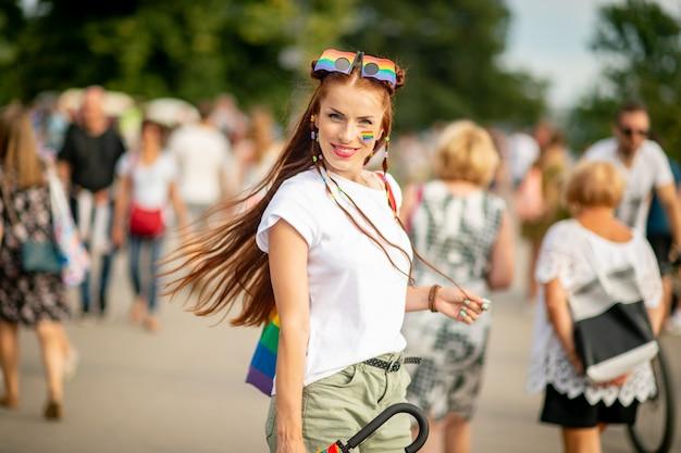 Retrato do estilo de vida de menina alegre com arco-íris lgbt no rosto, posando na rua