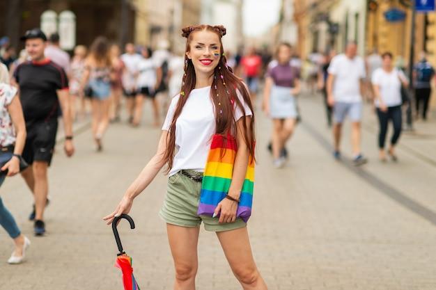 Retrato do estilo de vida de menina alegre com bandeira lgbt no rosto, posando na rua