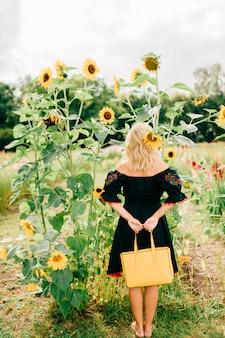 Retrato do estilo de vida de mulher loira incomum em bordado preto com ornamento segurando o saco de couro amarelo no jardim.